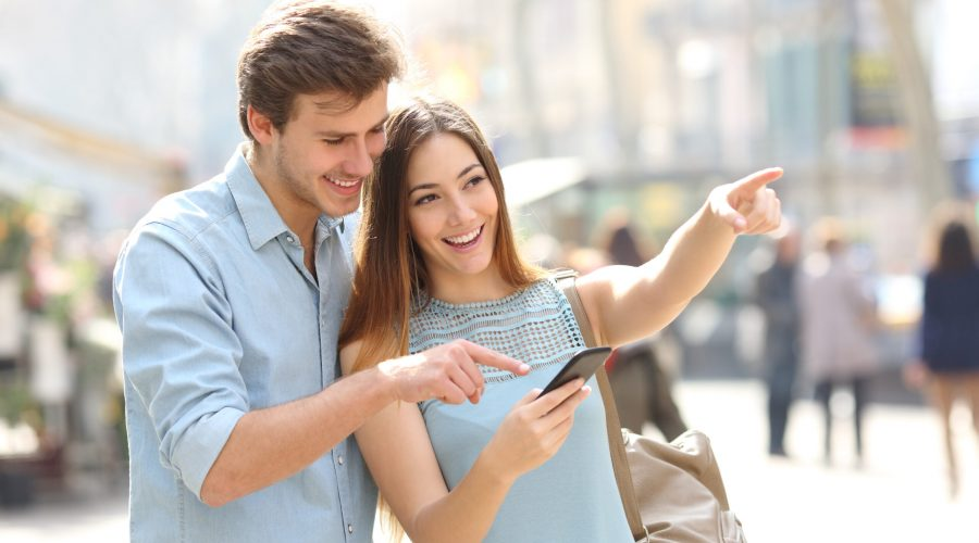 Happy friends or couple checking location on smart phone in the street